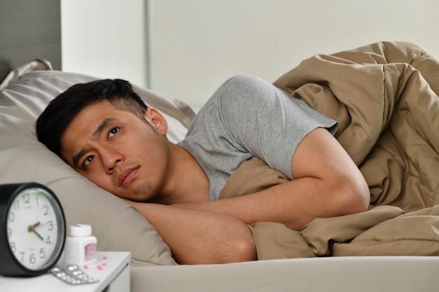 Depressiver junger asiatischer mann, der im bett liegt, kann vor schlaflosigkeit nicht schlafen