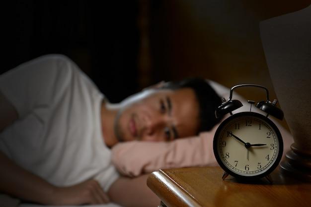 Depressiver mann, der an schlaflosigkeit leidet, die im bett liegt