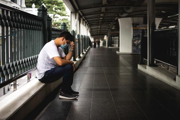 Depressiver mann, der auf dem gehweg des skytrain-bahnhofs sitzt trauriger mann, einsam und unglücklich konzept
