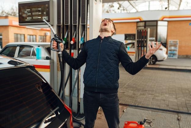 Depressiver mann weint an tankstelle, hoher kraftstoffpreis. benzintanken, benzin- oder dieseltankservice, benzintanken