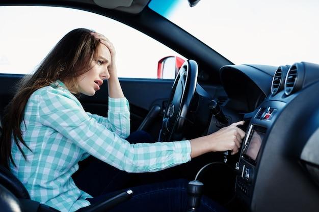 Depressives mädchen, das blaues hemd trägt, das im neuen auto sitzt, im verkehr, im porträt, in den motorproblemen feststeckt.