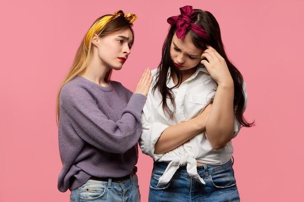 Depressives mädchen, das weint, weil es sich von seinem freund getrennt hat, während eine unterstützende freundin sympathie ausdrückt, mitleid mit ihr hat und sagt, dass alles in ordnung sein wird