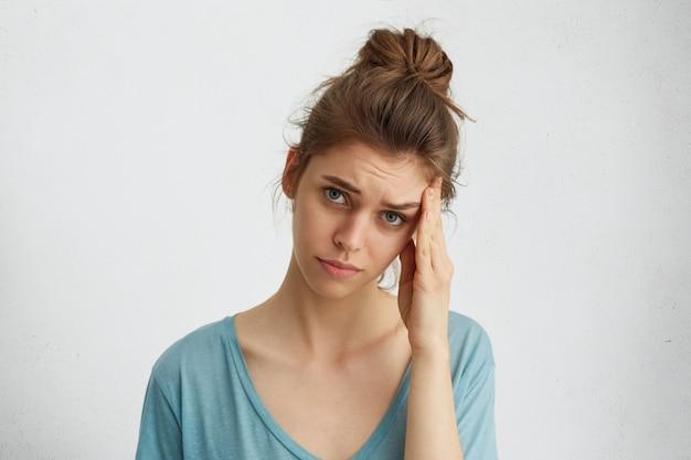 Deprimierende traurige frau mit haarknoten, blaue, erschöpfte augen, die ihren kopf berühren und unzufriedenen ausdruck haben, der müde ist