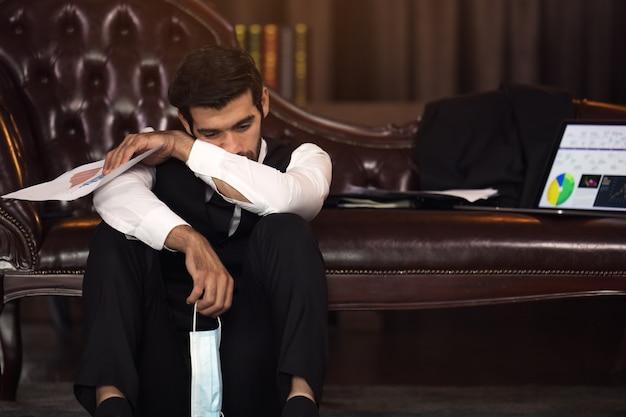 Deprimiert geschäftsmann mit geschlossenen augen händchen haltend auf kopf und papier mit diagrammen im amt