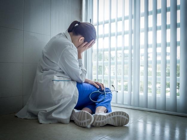 Deprimierte ärztin, die verzweifelt in der nähe eines krankenhausfensters sitzt - gesundheits- und trauerkonzept