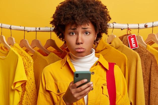 Deprimierte afro-frau nutzt smartphone zum online-shopping, unglücklich, steht gegen gelbe kleidung in kleiderbügeln