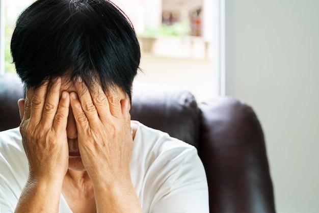 Deprimierte alte frau, hand der alten frau schließen ihr gesicht mit unglücklichem gefühl