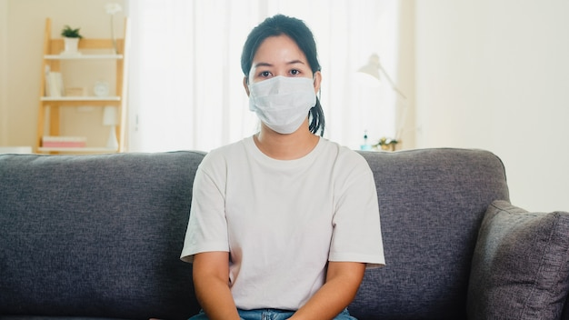 Deprimierte asiatische geschäftsfrau, die schutzmaske trägt, die auf sofa im wohnzimmer am haus sitzt, wenn soziale distanzierung zu hause bleibt und selbstquarantänezeit, pandemie in china, coronavirus-konzept.