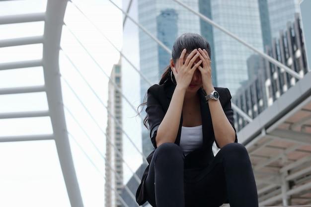 Deprimierte betonte junge asiatische geschäftsfrau