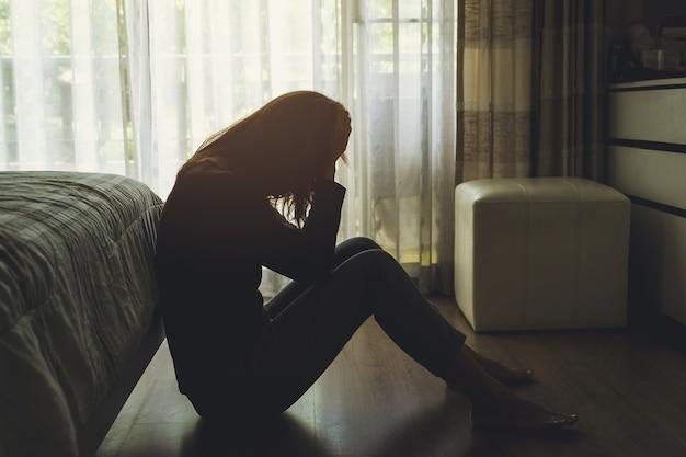 Deprimierte frau, die im dunklen schlafzimmer sitzt