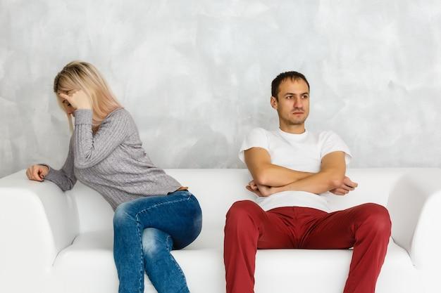 Deprimierte frau, die nach kampf mit dem ehemann sitzt auf couch beleidigt und traurig sich fühlt