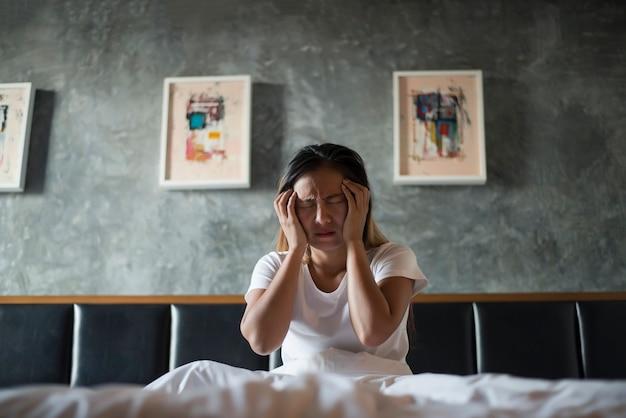 Deprimierte frau mit der kopfschmerzenhand, die ihren kopf auf dem bett hält