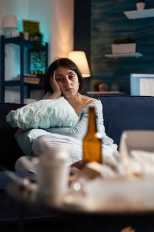 Deprimierte frustrierte gestresste traumatisierte frau, die allein sitzt und kissen hält holding