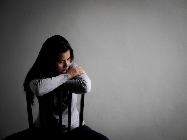 Deprimierte gebrochene herzige frau, die zu hause alleine in der dunkelkammer sitzt. einsam, traurig, liebe