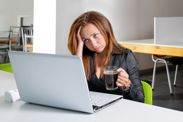 Deprimierte geschäftsfrau, die am computer sitzt