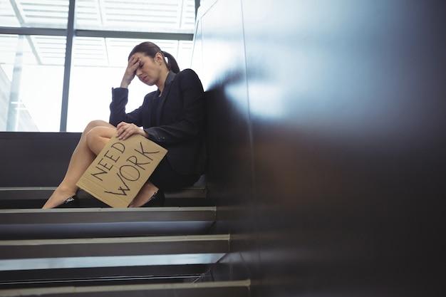 Deprimierte geschäftsfrau, die auf treppen sitzt, die kartonblatt mit text halten, brauchen arbeit