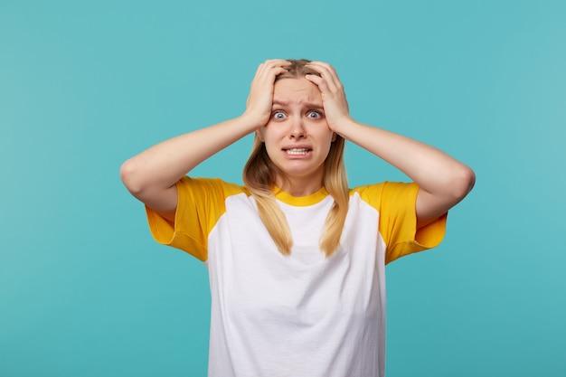 Deprimierte junge blauäugige blonde frau mit lässiger frisur, die ihren kopf mit erhobenen händen umklammert und ängstlich in die kamera schaut, isoliert über blauem hintergrund