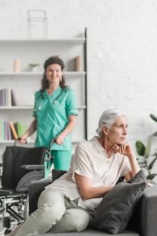 Deprimierte junge frau, die auf sofa vor der krankenschwester steht mit rollstuhl sitzt