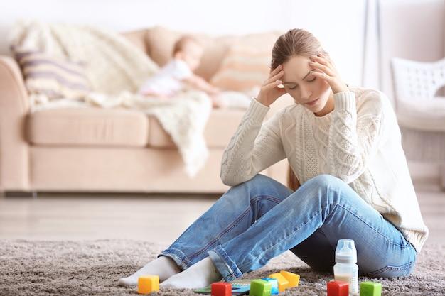 Deprimierte junge frau mit süßem baby zu hause