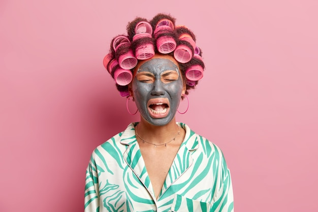 Deprimierte traurige frau weint laut und hat traurigen ausdruck, trägt schönheitsmaske auf gesichtshaarrollen auf und bereitet sich darauf vor, dass das datum verärgert ist, um mit ehemann zu brechen, der lässig isoliert auf rosa wand gekleidet ist