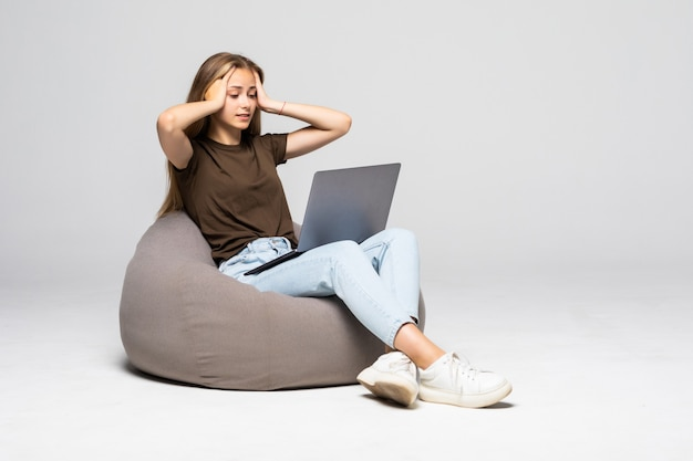 Deprimierte und frustrierte frau, die mit computer-laptop arbeitet, verzweifelt in der arbeit lokalisiert auf weißer wand. depression