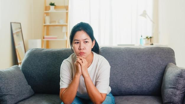 Deprimierte weinende asiatische frau gestresst mit kopfschmerzen, die auf sofa im wohnzimmer am haus sitzen