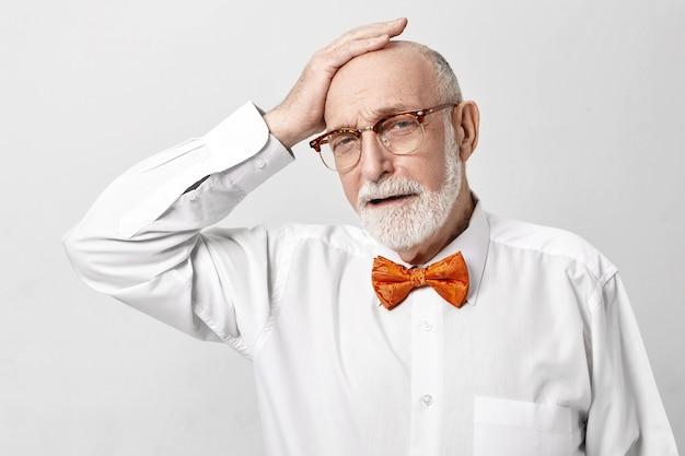 Deprimierter älterer 65-jähriger geschäftsmann mit dickem grauem bart, der unglücklichen schmerzhaften gesichtsausdruck frustriert hat