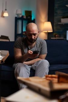 Deprimierter besorgter mann, der mieterbenachrichtigung für unbezahlte bankrechnungen liest