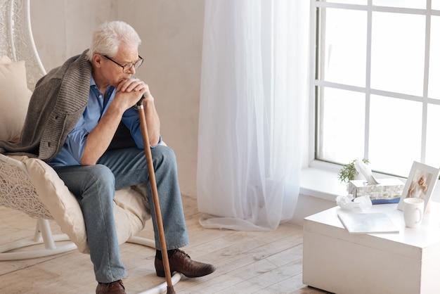 Deprimierter düsterer alter mann, der im sessel sitzt und das foto seiner frau betrachtet, während er sich auf den spazierstock stützt