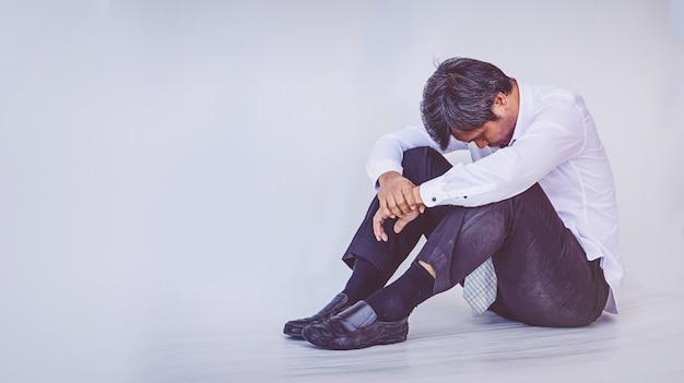 Deprimierter geschäftsmann, der auf dem boden sitzt