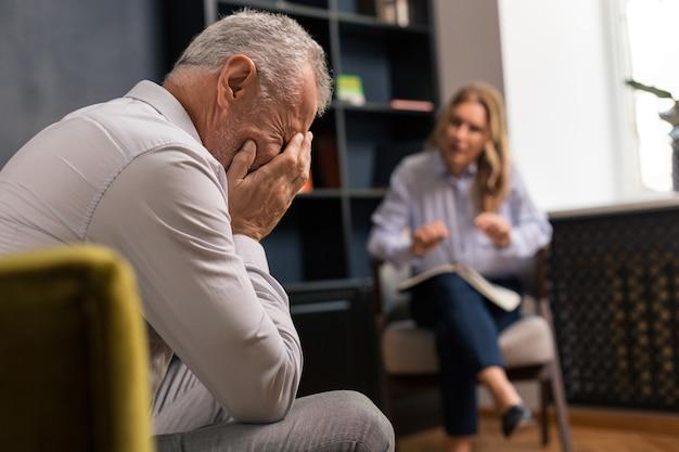 Deprimierter grauhaariger mann, der sein gesicht mit den händen bedeckt, während er einer blonden frau zuhört, die neben ihm sitzt