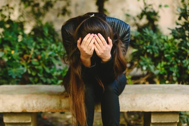 Deprimierter holdingkopf der jungen frau in den händen, die verletztem umkippen glauben