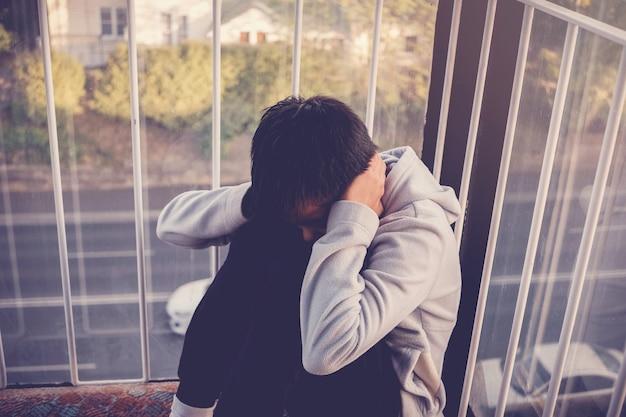 Deprimierter junger jugendlicher teenager, der seine ohren, kindergesundheit bedeckt