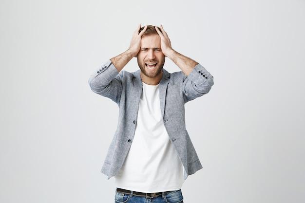 Deprimierter junger mann packt den kopf und schreit