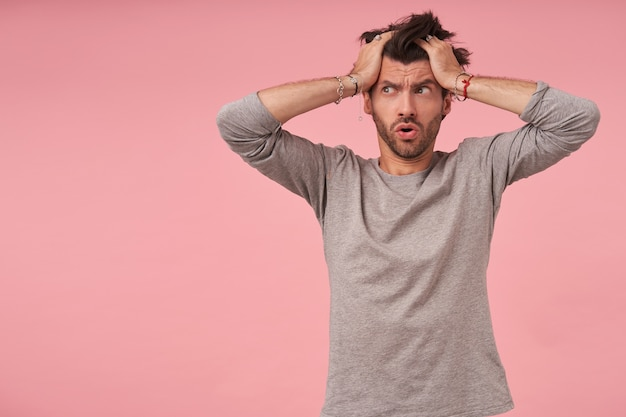 Deprimierter junger schöner mann mit bart, der mit handflächen auf seinem kopf steht, mit verzweifeltem gesicht zur seite schaut, stirnrunzeln und stirn zusammenzieht