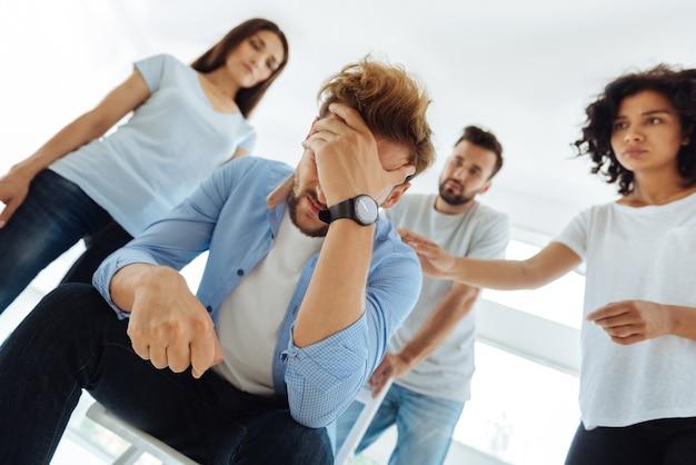 Deprimierter, launischer, unglücklicher mann, der seine stirn hält und darüber nachdenkt, wie er mit problemen umgehen kann, während er von seinen gruppenmitgliedern umgeben ist