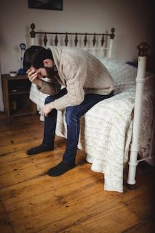 Deprimierter mann, der auf bett sitzt