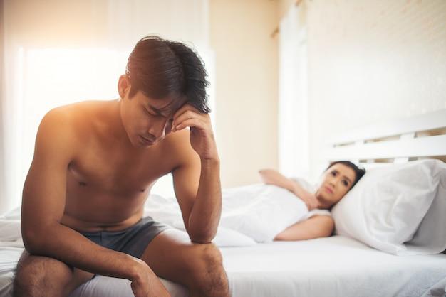 Deprimierter mann, der auf dem bett im schlafzimmer sitzt, haben problem mit seiner frau