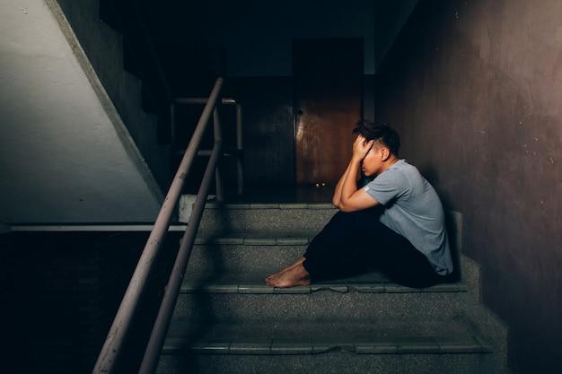 Deprimierter mann, der auf der treppe beim errichten sitzt und seine stirn beim haben von kopfschmerzen hält unterdrückungskonzept