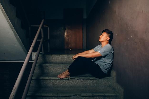 Deprimierter mann. trauriger mann, der auf der treppe im gebäude sitzt