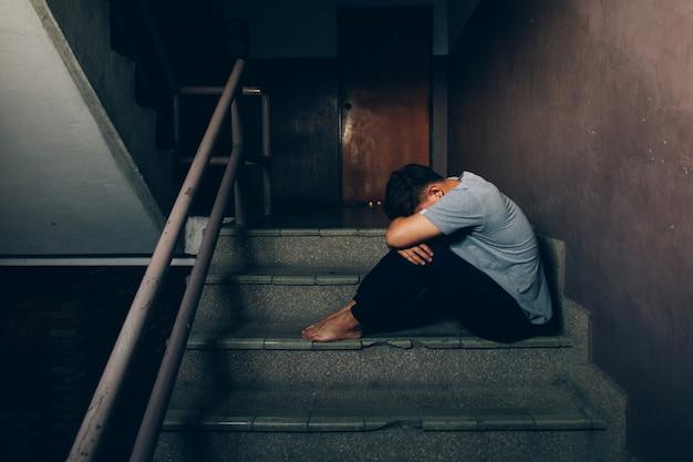 Deprimierter mann. trauriger mann, der ihre knie auf der treppe im gebäude umarmend sitzt