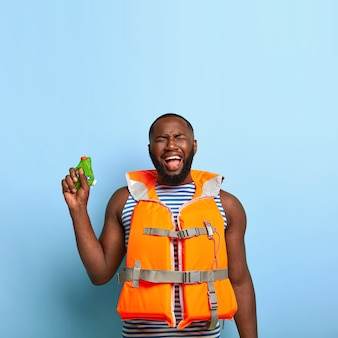 Deprimierter trauriger schwarzer mann fühlt sich unglücklich, wasserschlachtspiel zu verlieren