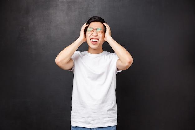 Deprimierter und angespannter junger asiatischer mann, der das lernen satt hat, viel im kopf hat, den kopf vor schmerz verzog, sich verzweifelt und verärgert fühlt, wut und störende gefühle ausdrückt,