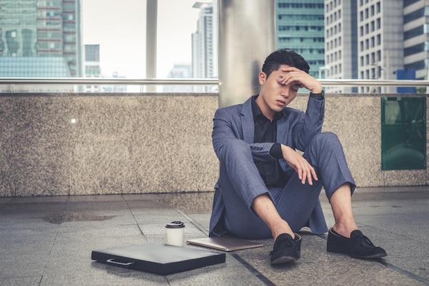 Deprimierter und müder geschäftsmann, der an der stadt sitzt