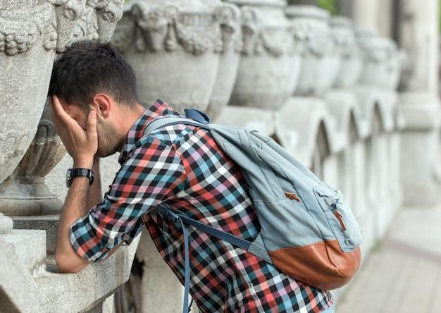 Deprimierter und verzweifelter mann, der sich an die wand lehnt