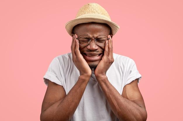 Deprimierter unglücklicher niedergeschlagener mann mit dunkler haut, stirnrunzeln unzufrieden