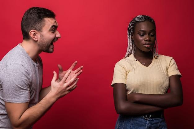 Deprimiertes junges paar gemischter rasse nach streit auf rotem hintergrund