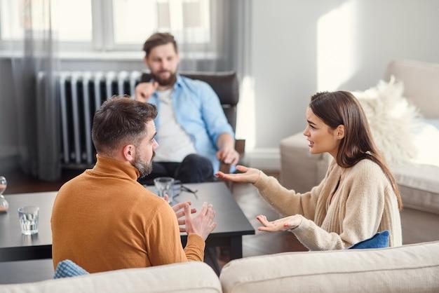 Deprimiertes junges paar von mann und frau, die mit psychologe auf therapiesitzung im modernen büro sprechen. schlechte beziehungen ohne zukunft.
