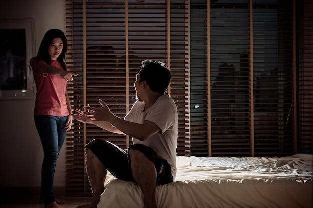 Deprimiertes paar ehemann und ehefrau streiten sich auf dem bett im dunklen schlafzimmer