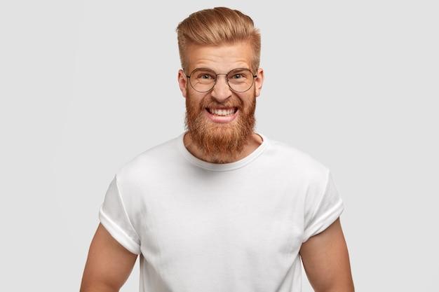 Deprimiertes, wütendes, irritiertes mannmodell mit dickem ingwerbart, starkem muskelkörper und zusammengebissenen zähnen